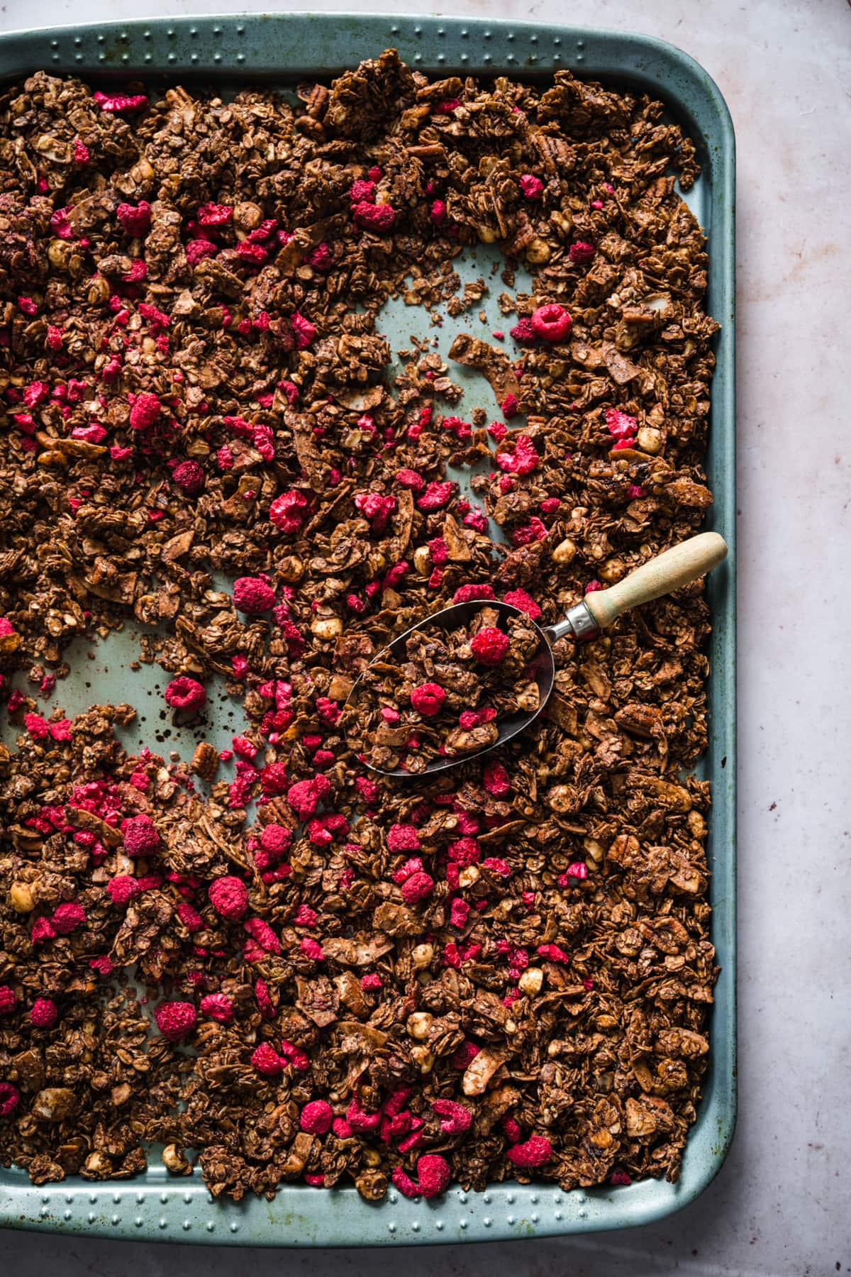 overhead view of chocolate hazelnut granola with freeze-dried raspberries on sheet pan.