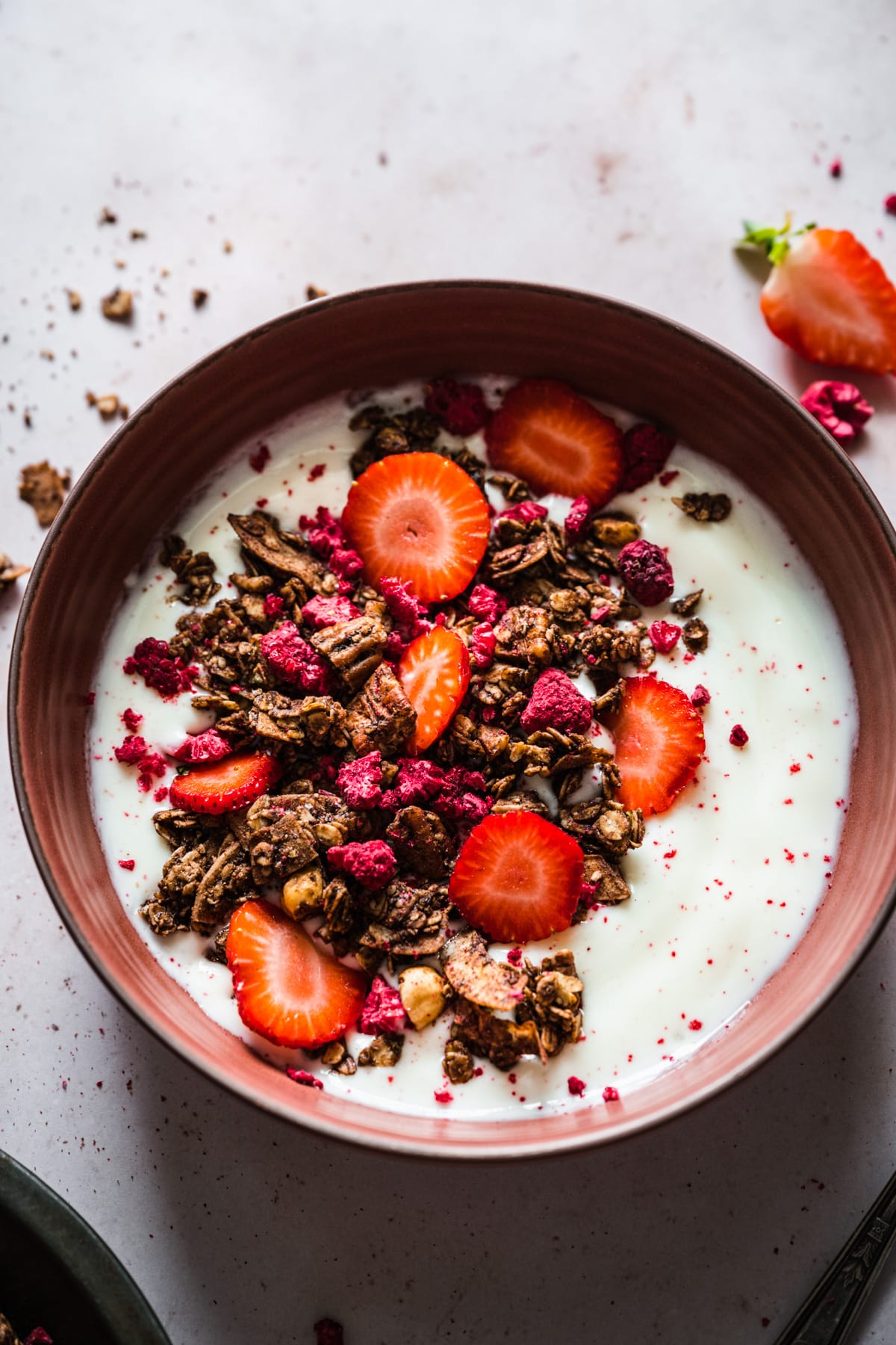 overhead view of chocolate hazelnut raspberry granola over yogurt with fresh strawberries.