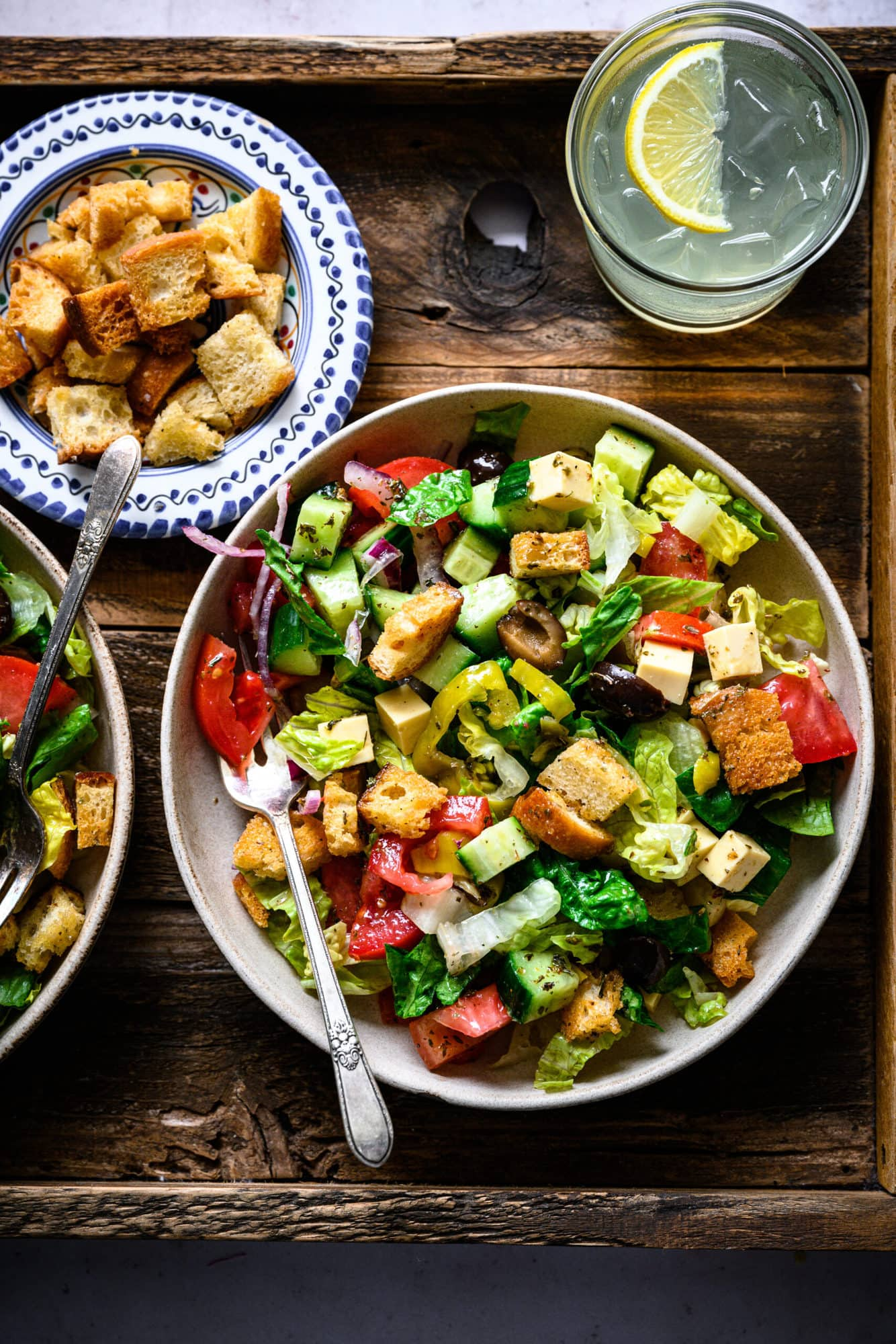 overhead view of vegan italian chopped salad in bowls on wood platter.
