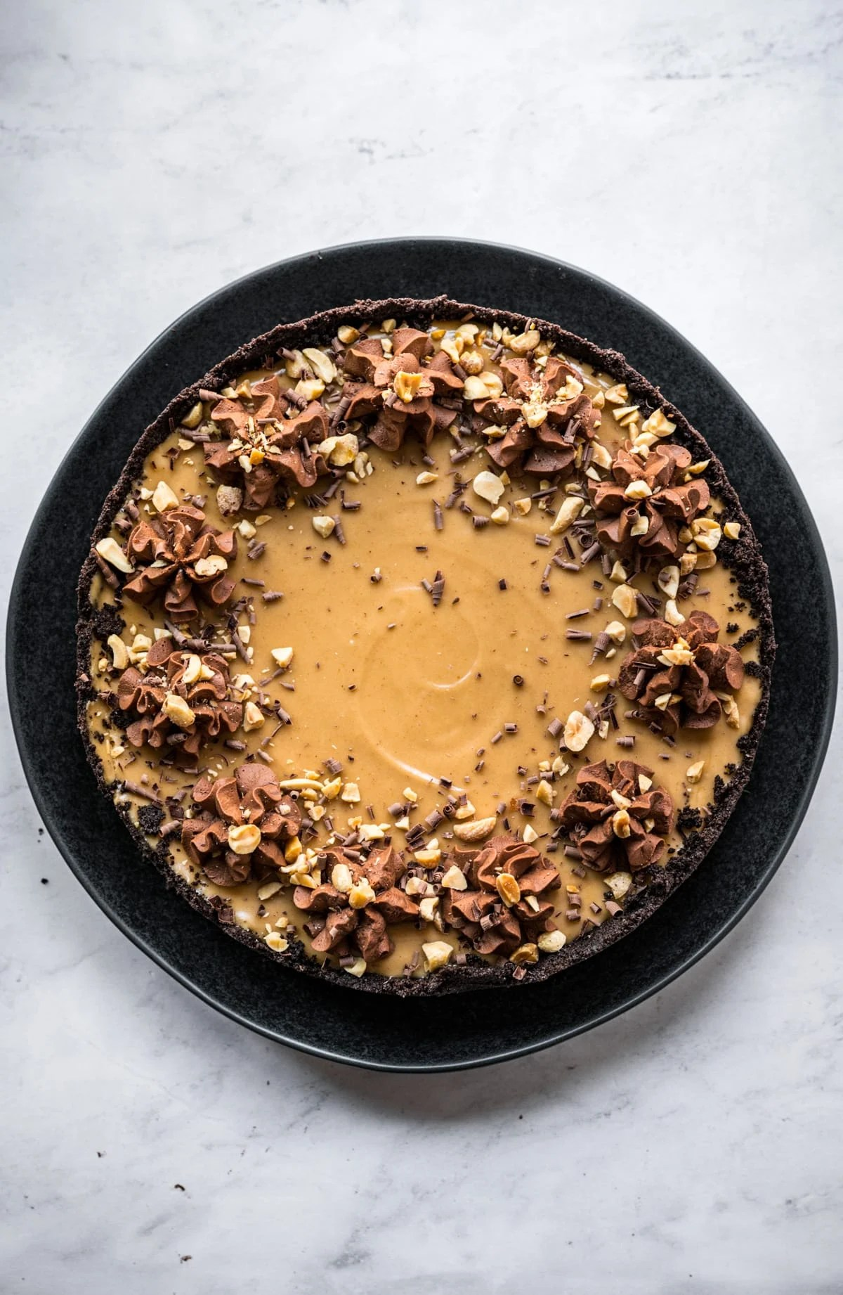 overhead view of vegan peanut butter pie with chocolate frosting on top.
