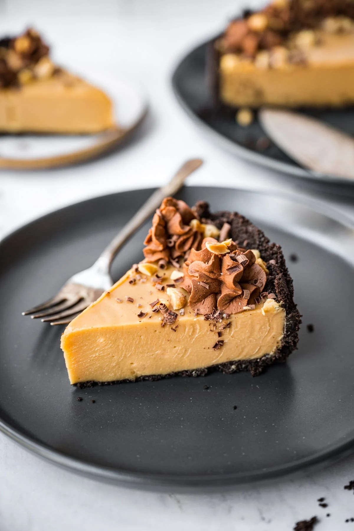 close up view of peanut butter pie with chocolate cookie crust on black plate.