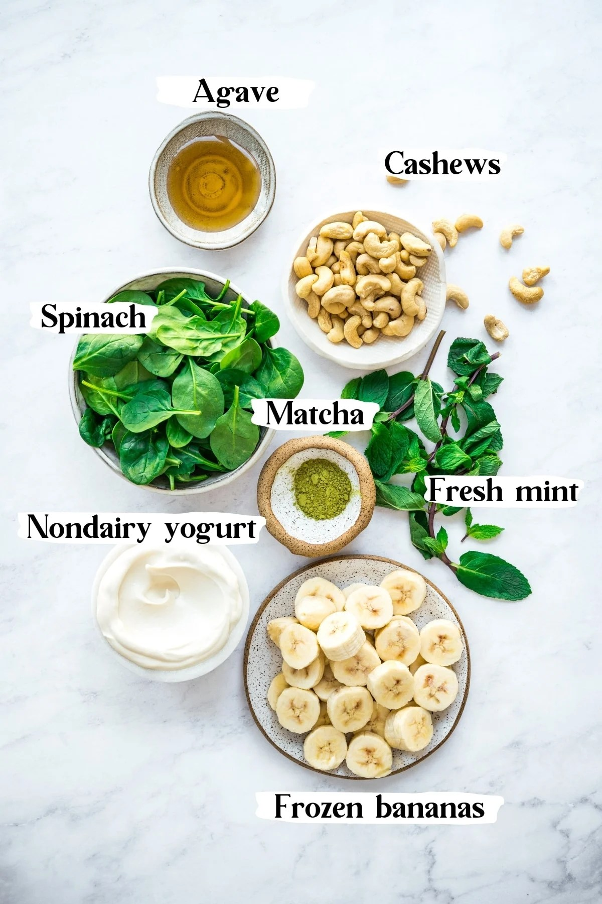 overhead view of ingredients for healthy shamrock shake, including frozen bananas, cashews, mint, spinach and yogurt.