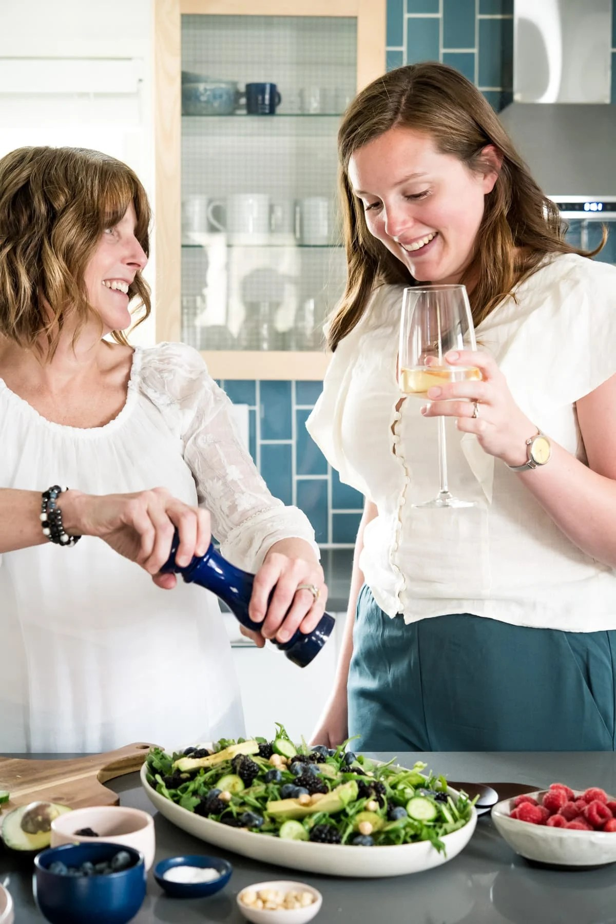 headshot of Lexi and Beth from Crowded Kitchen in the kitchen with wine.