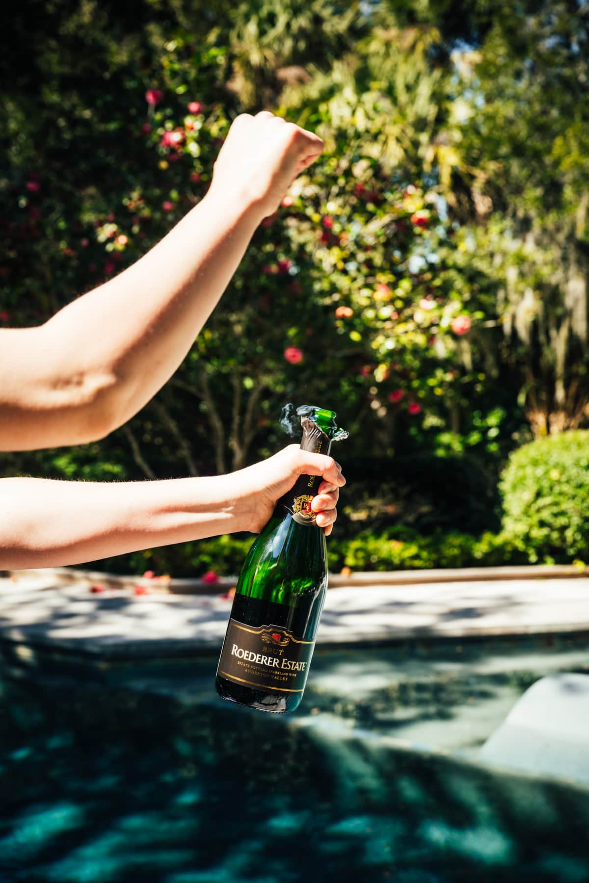 person opening bottle of champagne in front of pool.