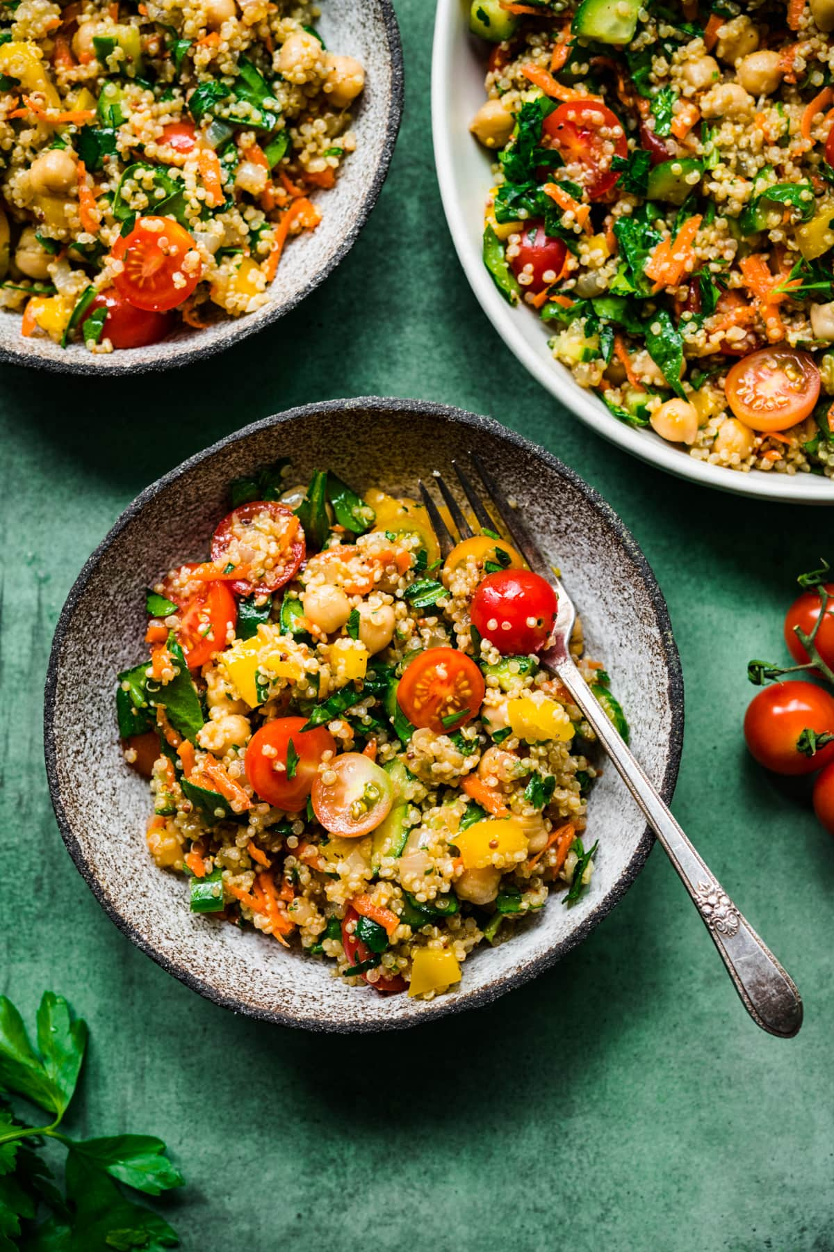 overhead view of vegan quinoa chickpea salad with vegetables in a bowl on green backdrop.