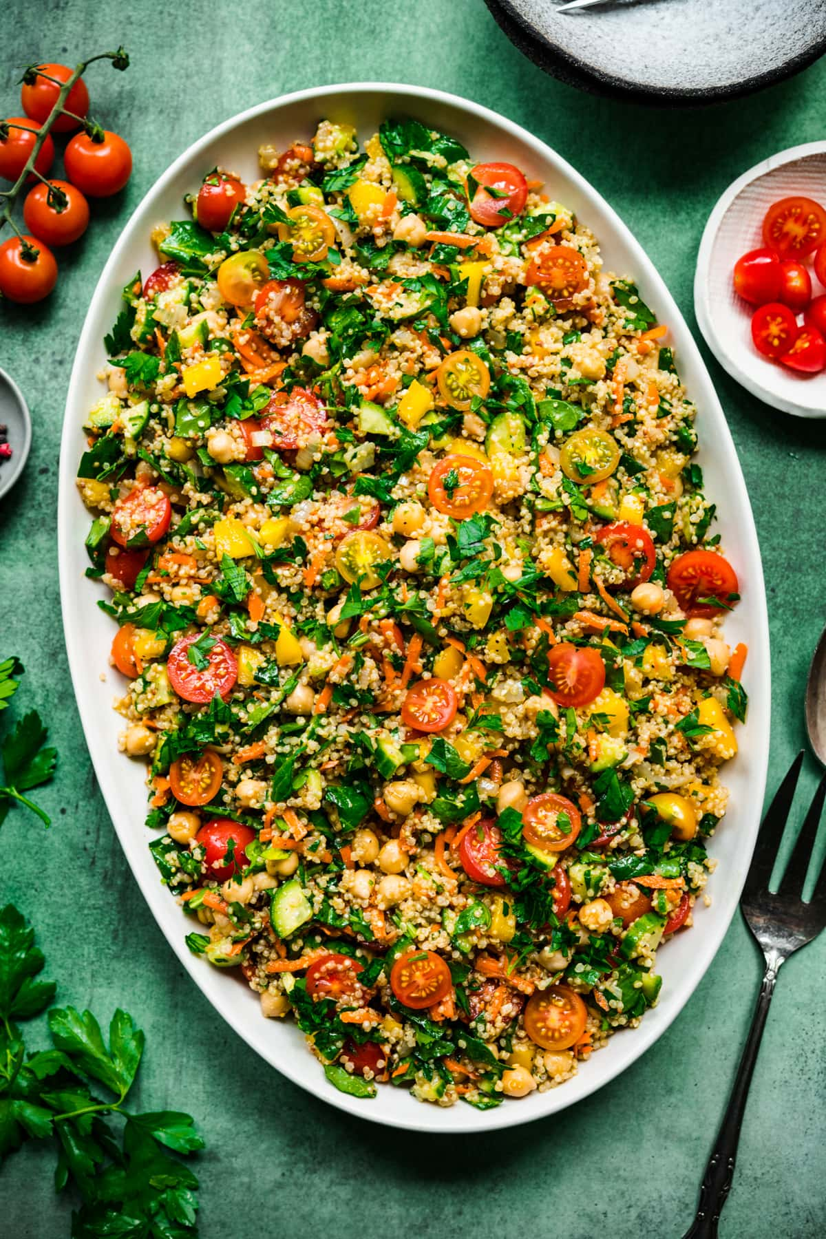 overhead view of quinoa chickpea vegetable salad on a large white platter on green backdrop.