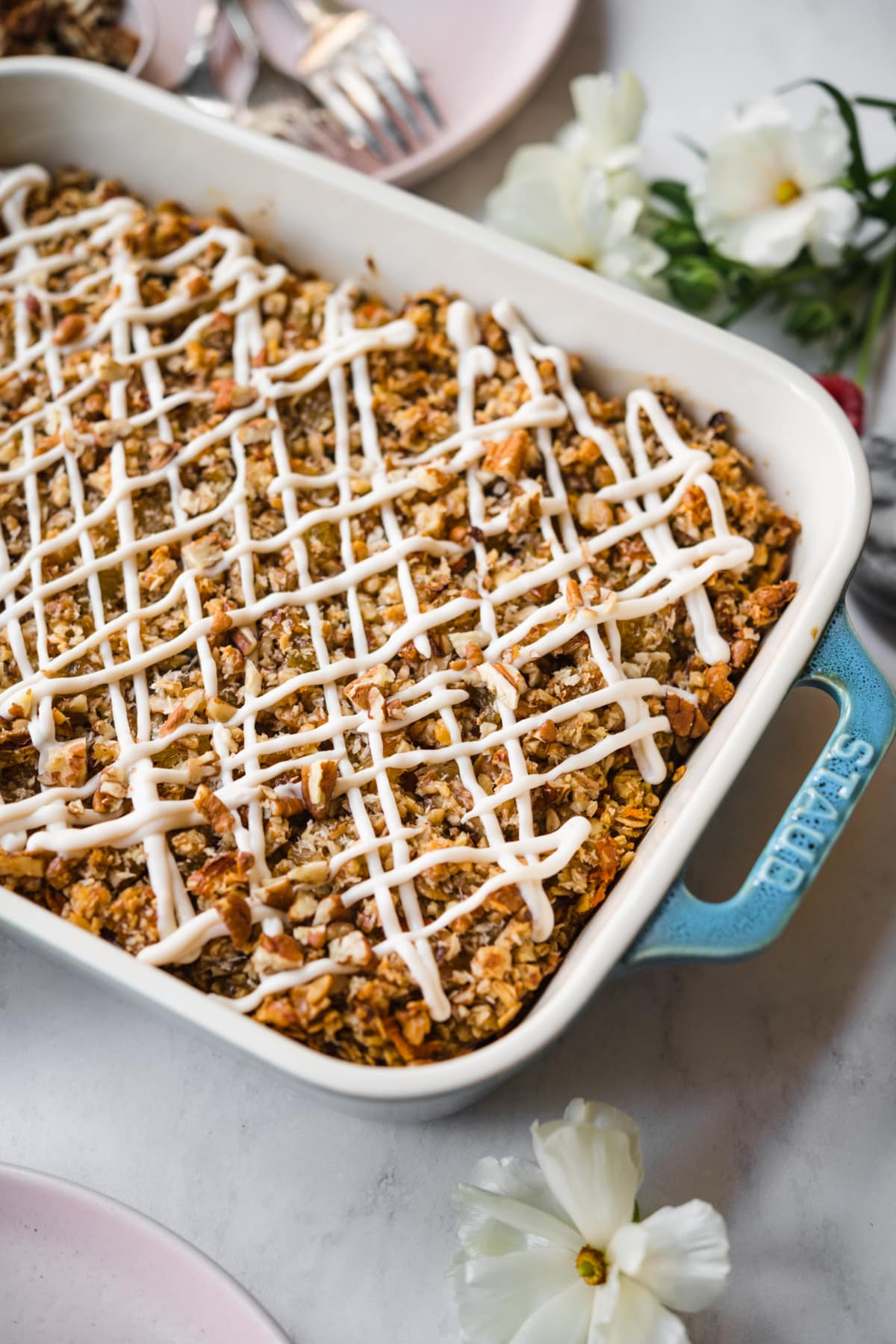 close up view of vegan carrot cake baked in a blue baking dish with cream cheese glaze.