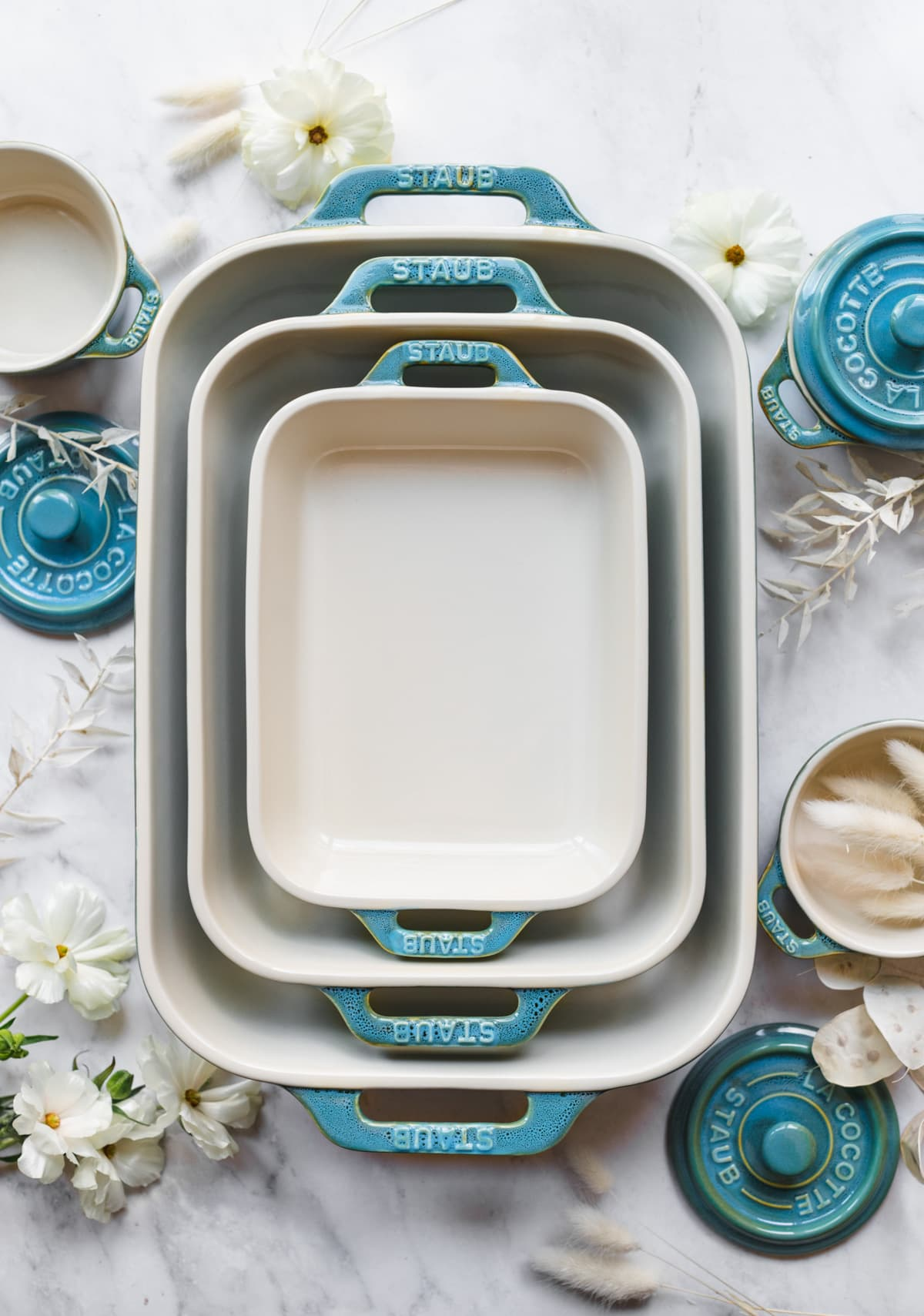 overhead view of Staub turquoise ceramic baking dishes and cocottes on marble surface.