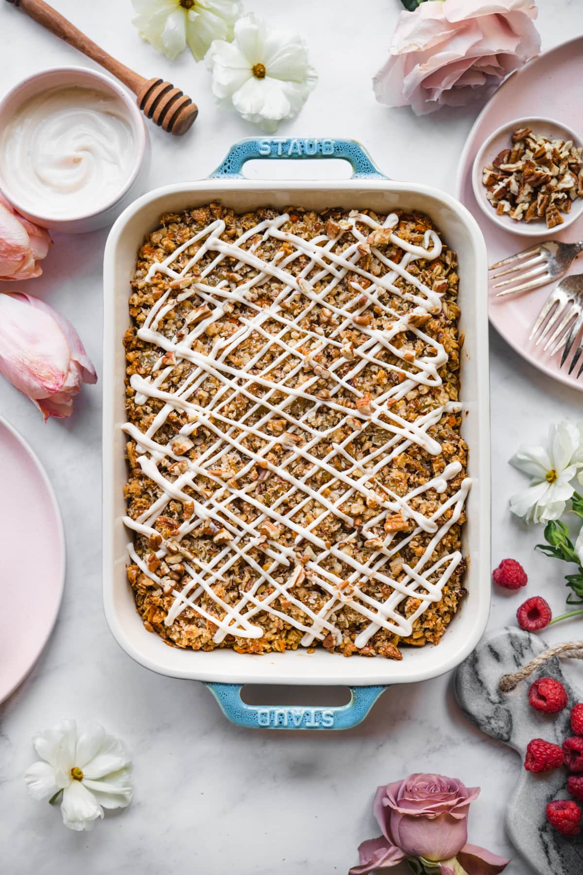 overhead view of vegan carrot cake baked in a blue baking dish with cream cheese glaze.