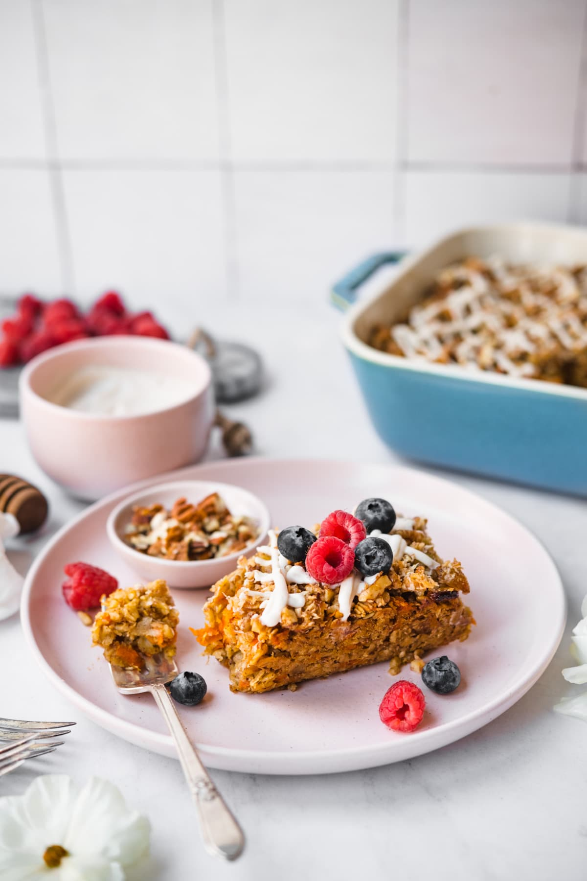 slice of vegan carrot cake baked oatmeal with fresh berries on top on a pink plate.