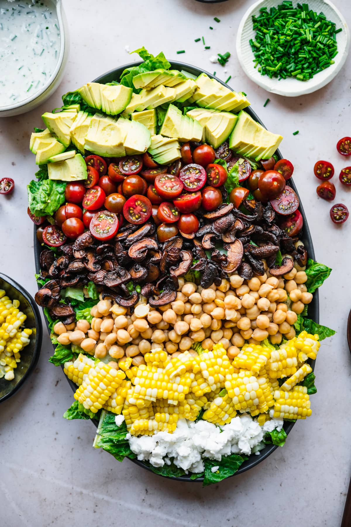 overhead view of vegan cobb salad on a platte with corn, chickpeas and mushroom bacon.