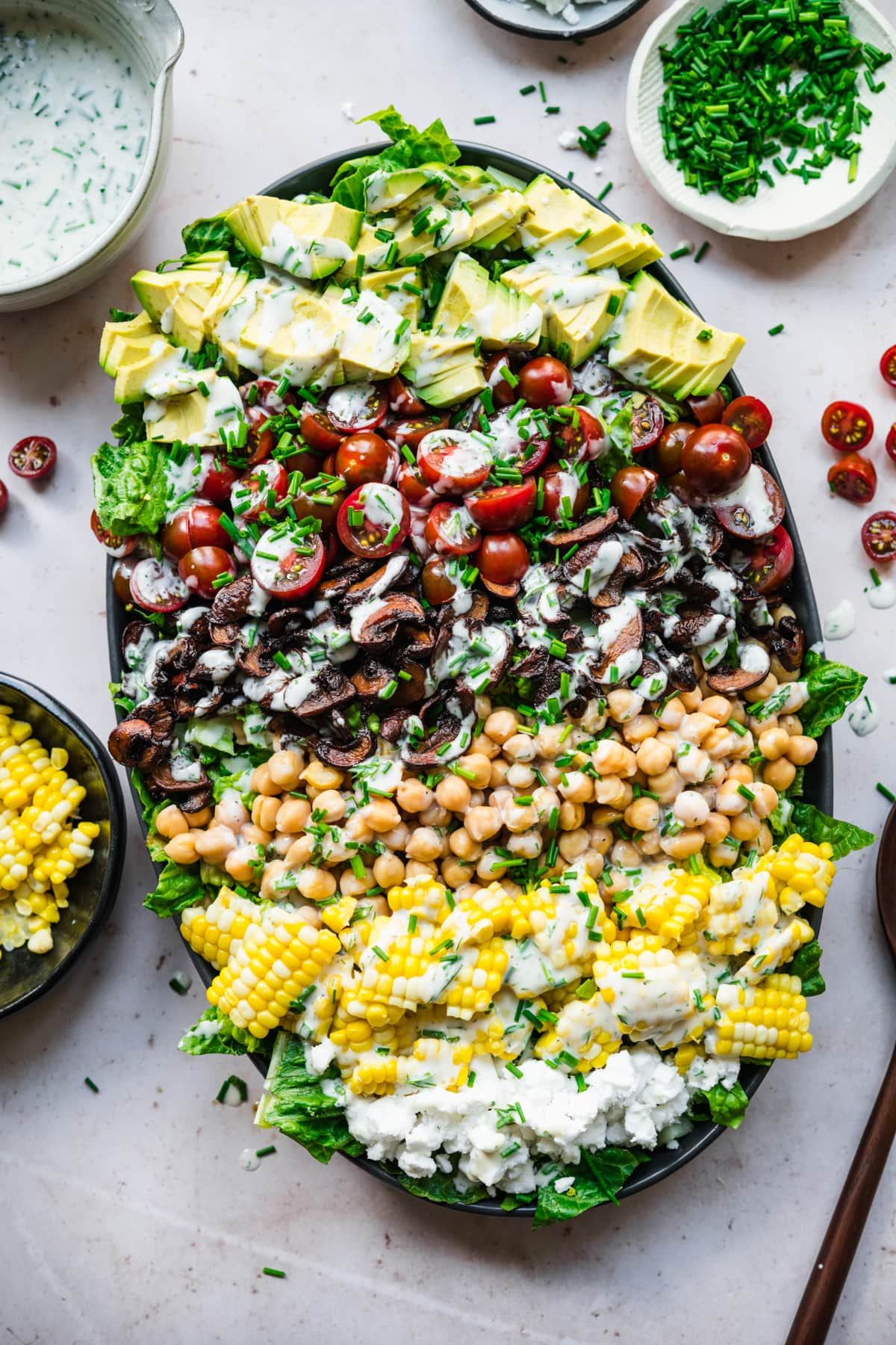 overhead view of vegan cobb salad on a platter topped with vegan ranch dressing.