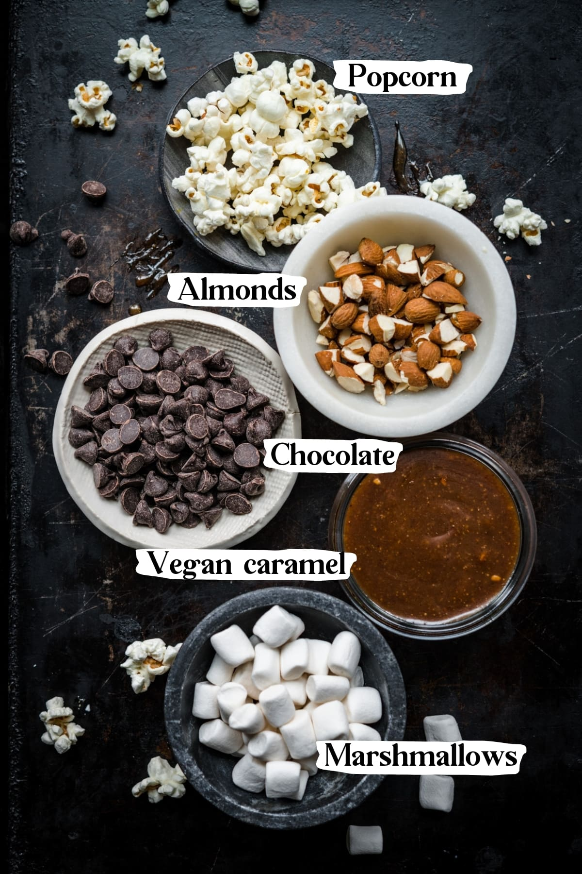 overhead view of popcorn, almonds, chocolate chips, caramel sauce and marshmallows in separate small bowls.