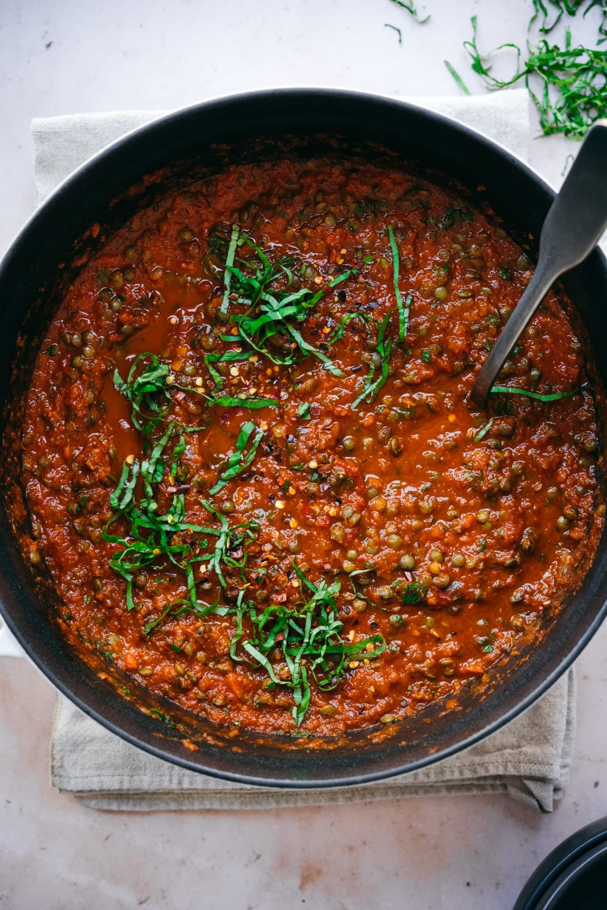 overhead view of vegan lentil bolognese sauce in large pot topped with fresh basil.