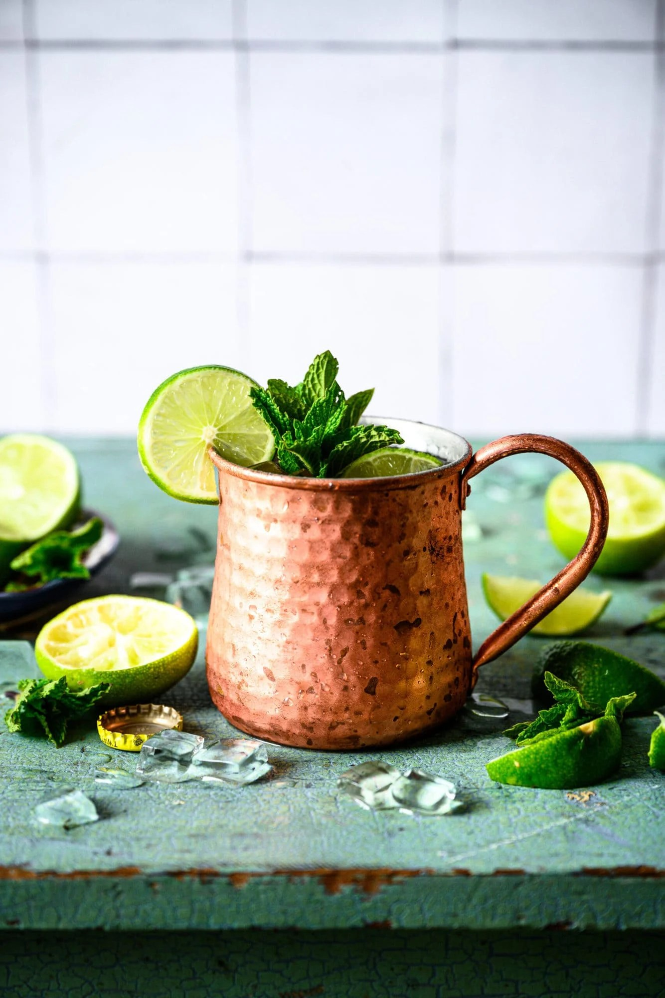 One tequila mule cocktail in copper mug with lime and mint garnish on antique blue table.