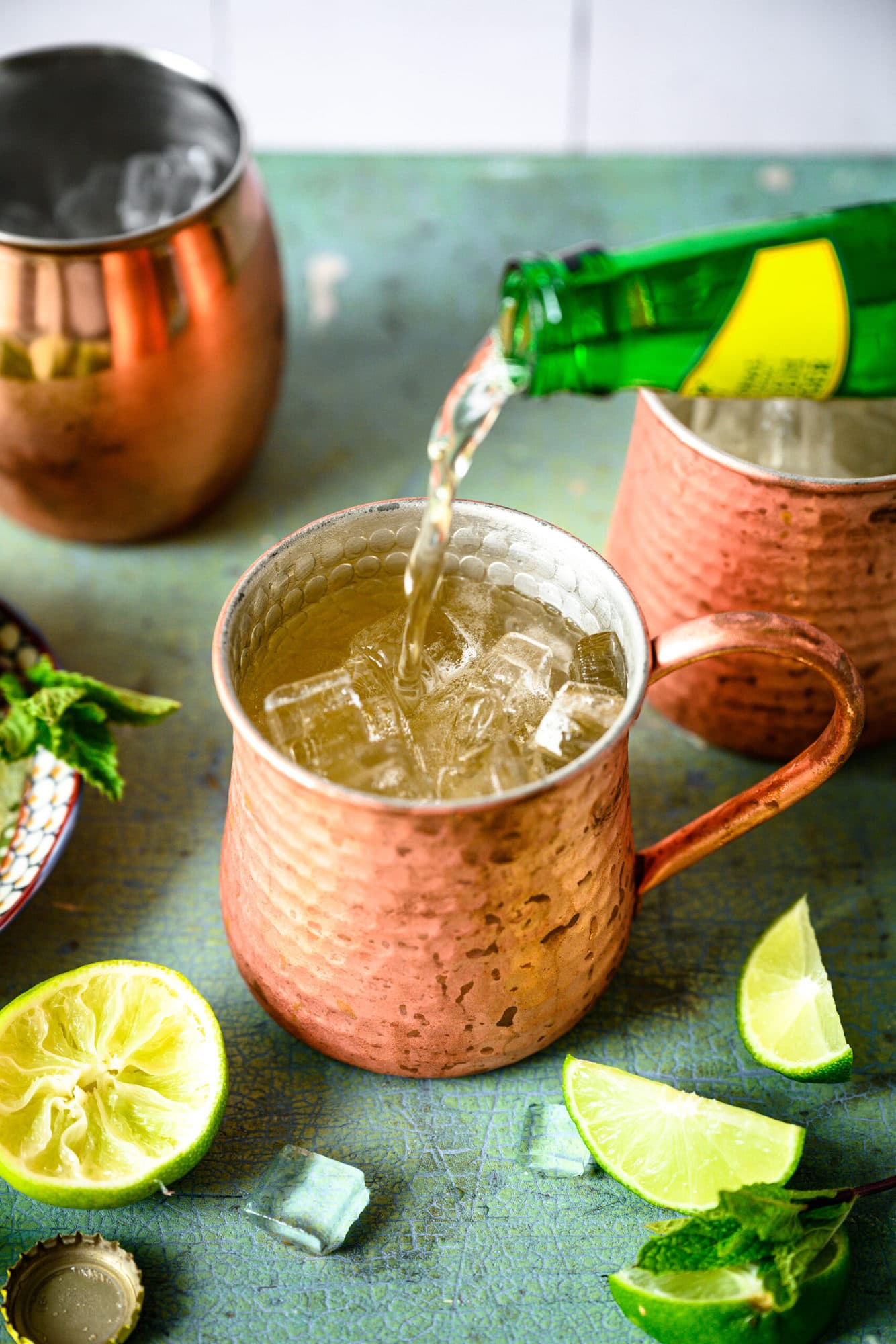 pouring ginger beer into tequila mule cocktail in copper mug.