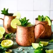 Two tequila mule cocktails in copper mugs with lime and mint garnish on antique blue table.