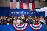 People Listen to President Barack Obama as he delivers remarks on the American Jobs Act 2012
