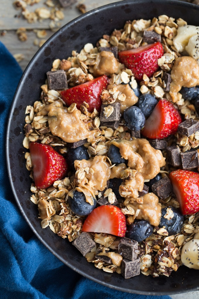 Up-close overhead view of granola and fruit in a black bowl.