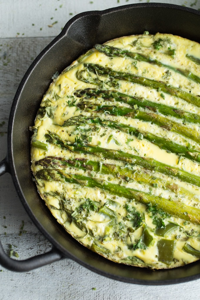 Overhead view of the baked Green Goddess Crustless Quiche in a black cast iron pan on a white wooden surface.