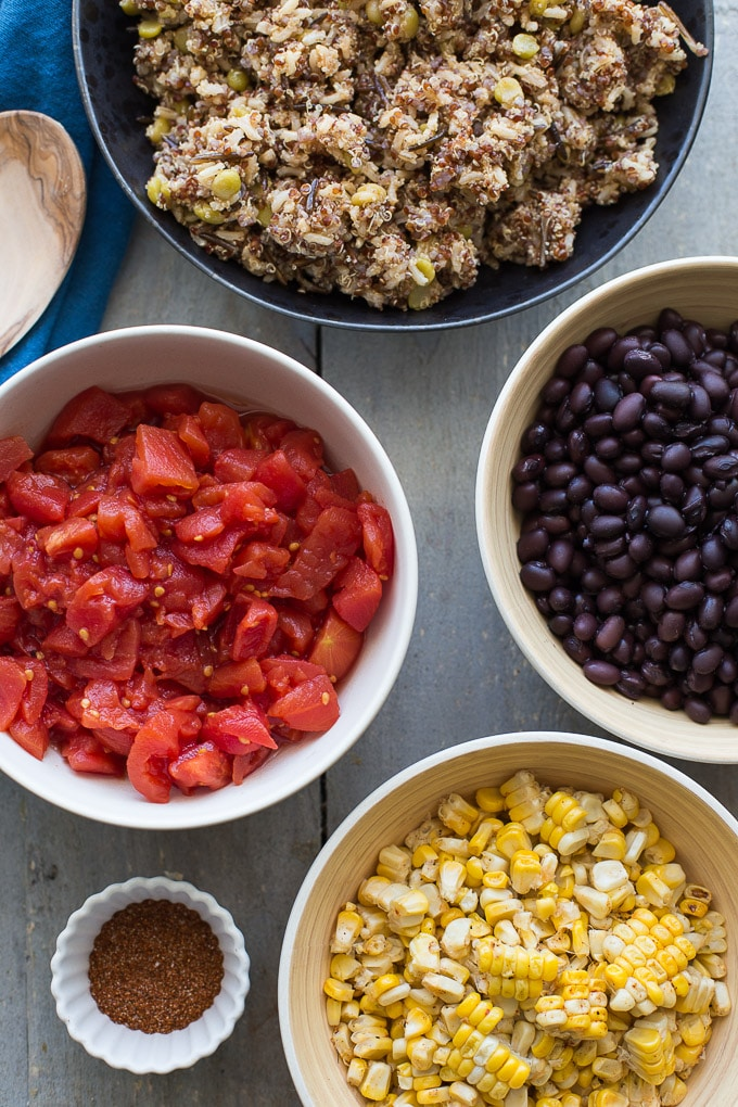 Individual bowls of tomatoes, quinoa, black beans, corn and spices arranged on a wooden surface.