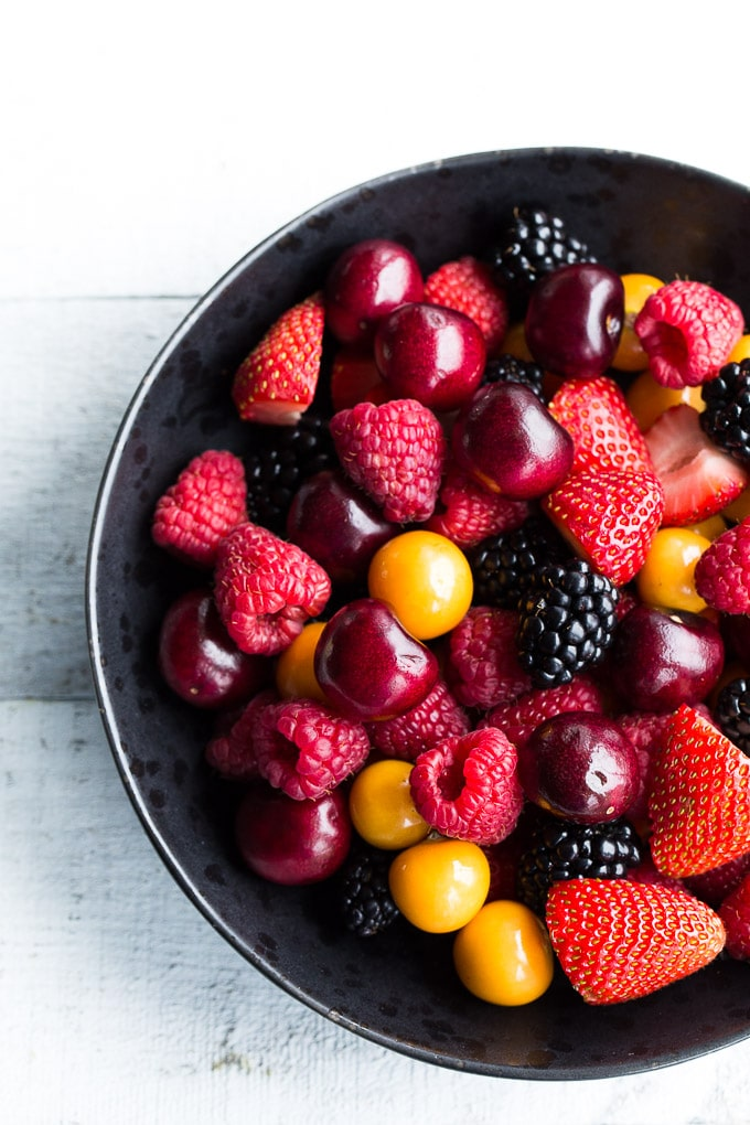 Overhead view of cherries and berries in a black bowl on a white, wooden surface.