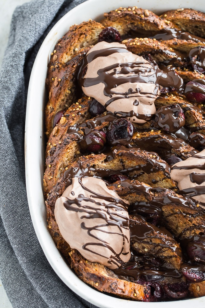 Up-close view of the Dark Chocolate Cherry French Toast Bake out of the oven and topped with dark chocolate and cream.