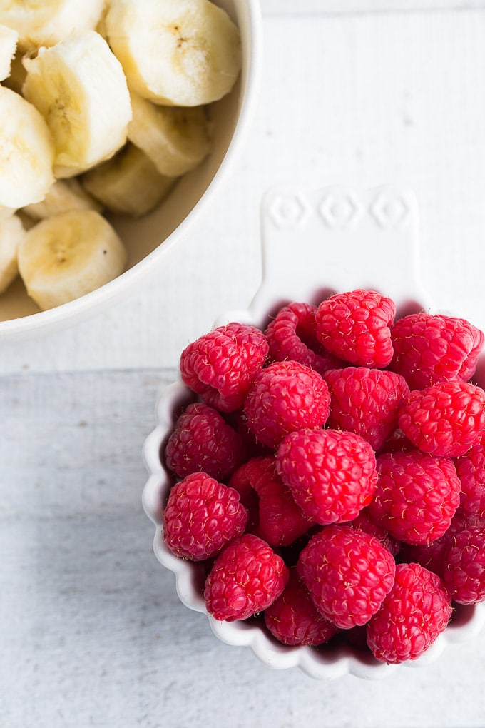 Overhead view of bowls of raspberries and chopped bananas on a white wooden surface.