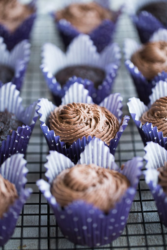 Side view of Chocolate Zucchini Cupcakes, some with coconut whip, on a wire rack.