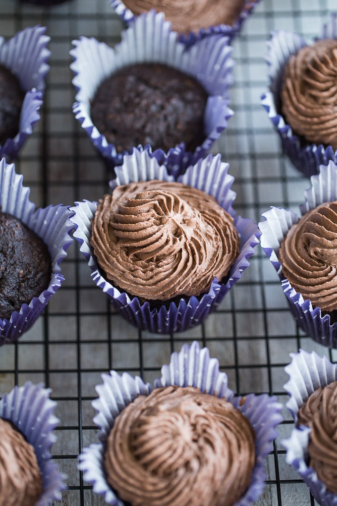 Overhead view of Chocolate Zucchini Cupcakes, some with coconut whip, on a wire rack.