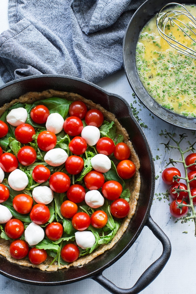 Overhead view of Tomato, Arugula and Mozzarella Quiche being assembled in a cast iron pan. A bowl of scrambled eggs next to it.