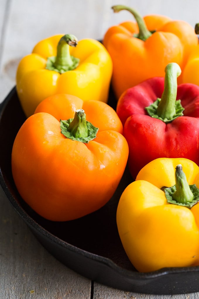 Up close view of yellow, orange and red whole bell peppers.