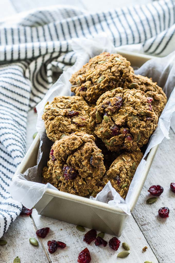 Up-close view of Avocado Pumpkin Oatmeal Breakfast Cookies arranged in a loaf pan with a blue and white towel surrounding it.