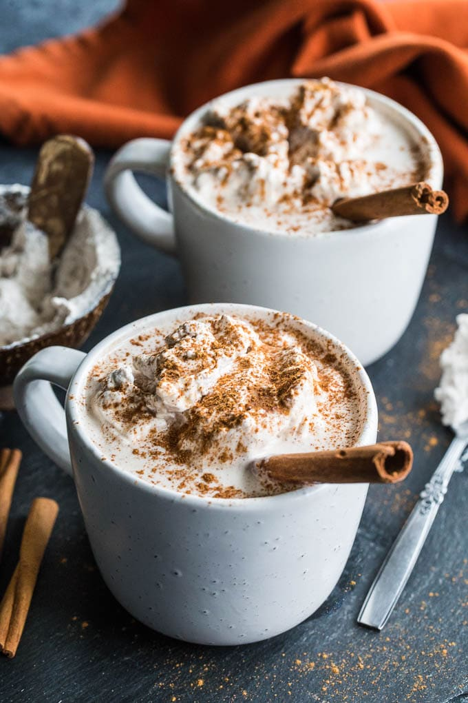 Two Pumpkin Spice Collagen Lattes topped with coconut whip, pumpkin spice and a cinnamon stick.