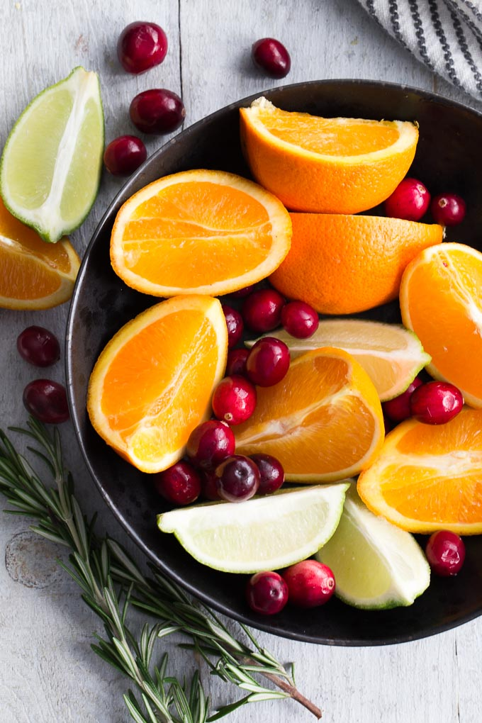 Overhead view of cranberries and orange and lime wedges in a black bowl on a white surface.