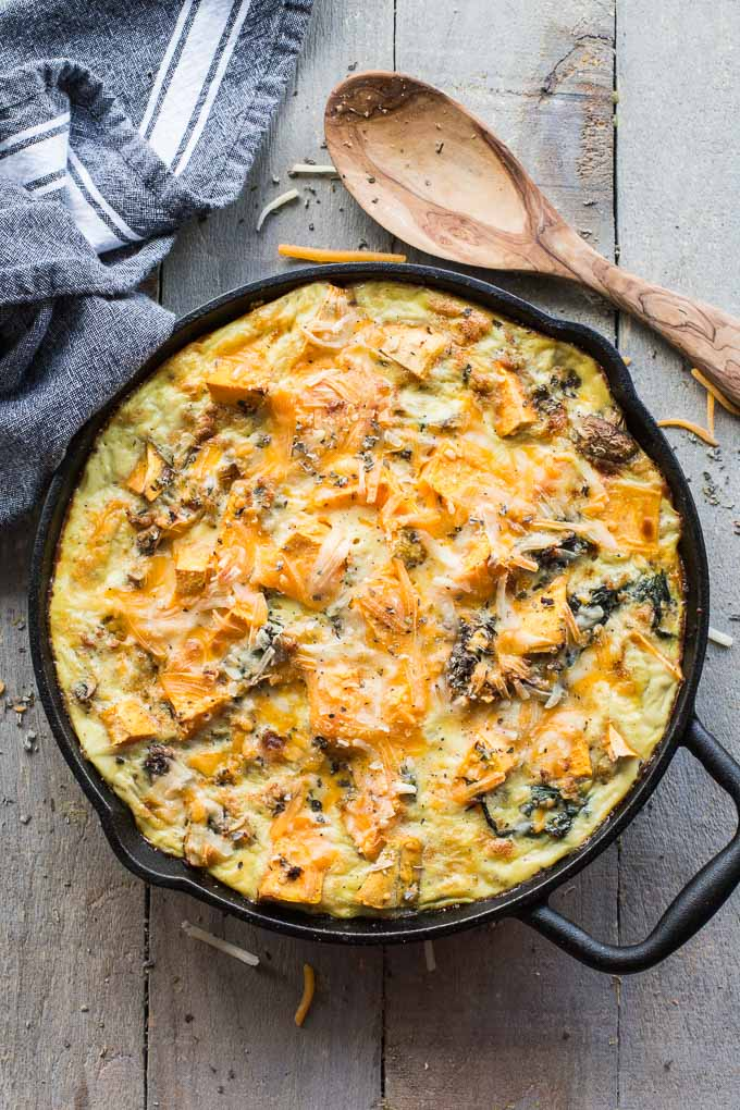 Overhead view of Sweet Potato Turkey Egg Bake in a cast iron skillet on a wooden surface.