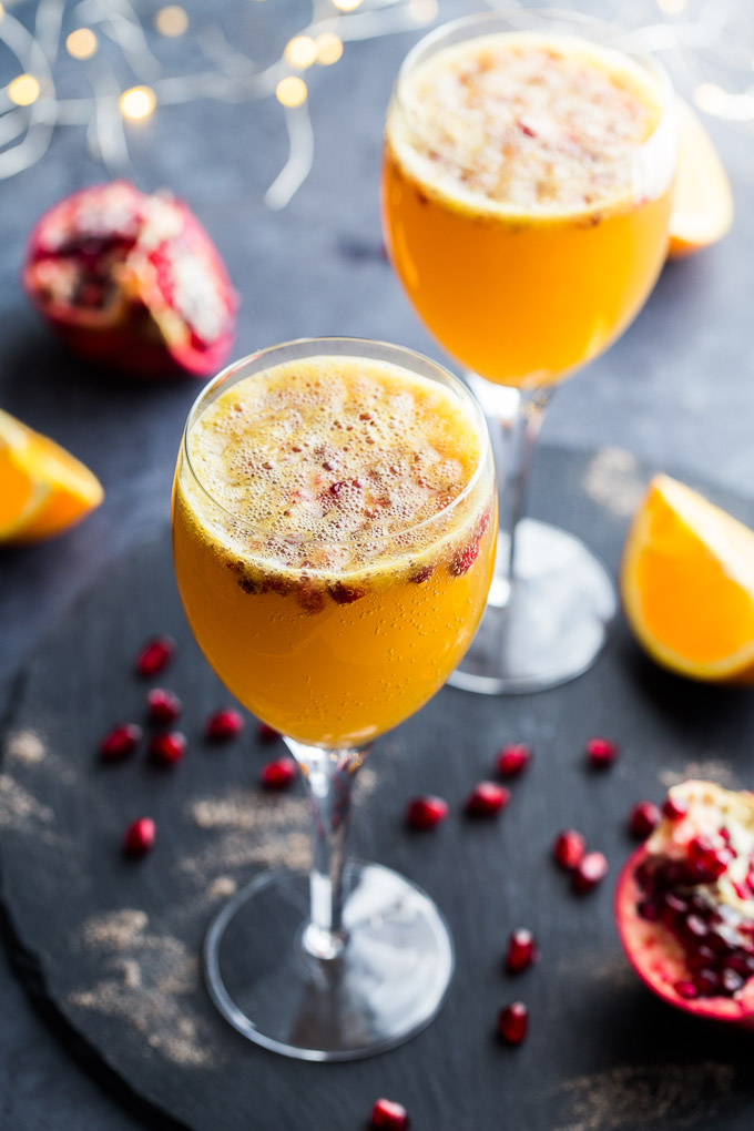 Two Ginger Beer Mimosas in wine glasses on a dark surface, surrounded by pomegranate arils.