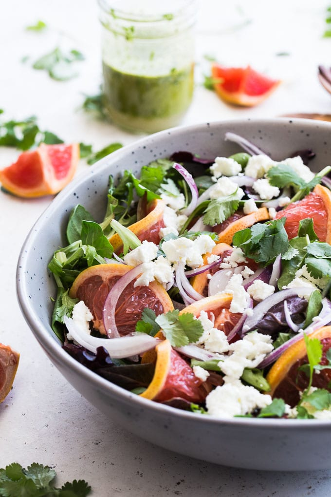 Up-close side view of Grapefruit Salad with Cilantro and Goat Cheese in a grey bowl.