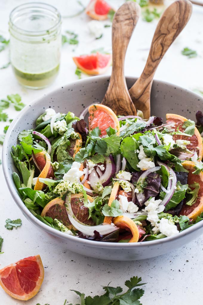 Grapefruit Salad with Cilantro and Goat Cheese in a large grey bowl with a jar of cilantro dressing in the background.