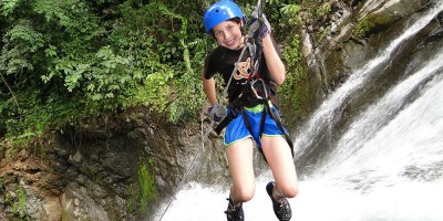 Youg girl rappelling beside a waterfall