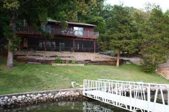 Lakeside of home, with grassy yard, screened in porch and shaded upper deck