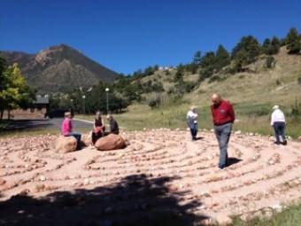 labyrinth at Franciscan Retreat Center, Colorado Springs, shows several people praying and walking in circles around it. At the center are three women sitting on rocks.