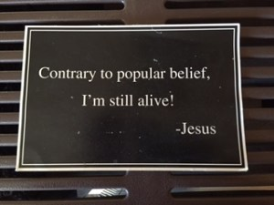 "Black sign with white letters says, ""Contrary to popular belief, I'm still alive! --Jesus"""