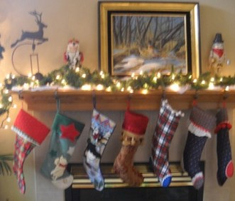 Seven different stockings hang from a lit mantle with evergreen, two nutcrackers and a metal reindeer.