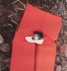 A little girl's white patent shoe rests on a red life preserver surrounded by rocks.