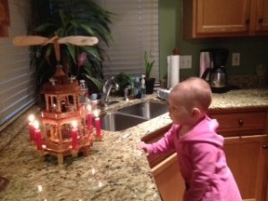 A toddler, in pink hoodie, stands at kitchen counter, pondering the wooden nativity carousel, lit with red candles.