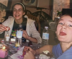 Two junior high girls hold their eggs, one smiling and one sticking out her tongue. There are lit candles on the table, pysanky tools and bottled water.