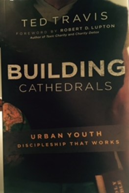 """Black Book Jacket, with tan lettering for title Building Cathedrals, above are grey letters for Ted Travis and below in orange letters are: """"Urban Youth, Discipleship That Works"""""""
