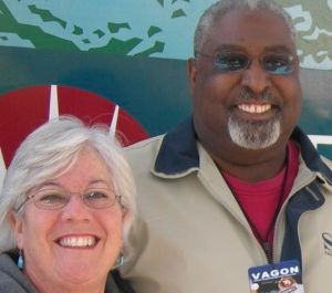 Smiling, older couple Shelly, left, and Ted Travis. He is a husky black man with white/black beard and glasses. She has white, short cropped hair, glasses, wearing dangling blue earrings.