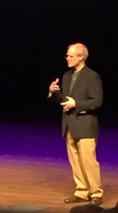 Andrew Clements stands on stage at Calvin College.